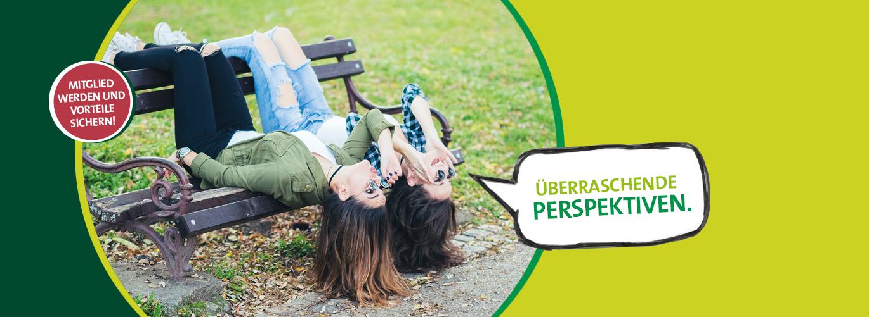 Zwei Frauen liegen kopfüber auf einer Parkbank